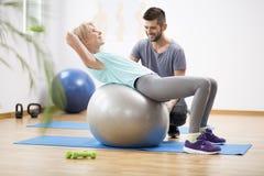 Middenleeftijds blonde vrouw die op gymnastiek- bal tijdens zitting met fysiotherapeut uitoefenen stock fotografie