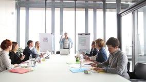 Middenleeftijds creatieve directeur die op een vergadering met collega's bespreken stock video
