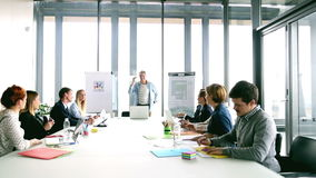 Middenleeftijds creatieve directeur die op een vergadering met collega's bespreken stock footage