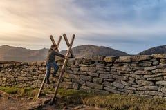 Middenleeftijdsmens die een ladder op de steenmuur beklimmen in bergen, die tot de toekomst, zonsondergang in de bergen bereiken stock fotografie