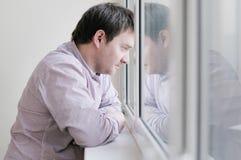Middenleeftijdsmens die het venster bekijken Royalty-vrije Stock Afbeelding