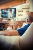 Middenleeftijdsmens die op TV letten Royalty-vrije Stock Foto's