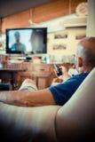Middenleeftijdsmens die op TV letten Royalty-vrije Stock Afbeelding