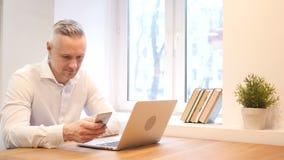 Middenleeftijdsmens die Smartphone gebruiken op het Werk stock footage