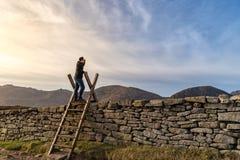 Middenleeftijdsmens die zich op de ladder op de steenmuur bevinden in bergen, die omhoog in de afstand, zonsondergang in het berg stock foto's