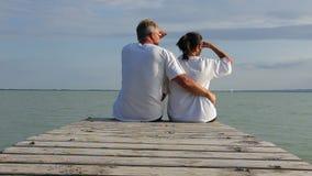 Middenleeftijdspaar op de pijler in een meer Balaton van Hongarije bij zomer stock video