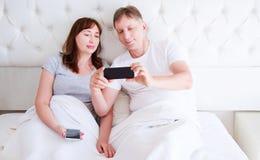 Middenleeftijdspaar, vrouw en man die smartphone gebruiken bij slaapkamer Ultra breed huisschot stock foto