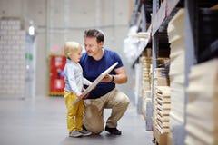 Middenleeftijdsvader met weinig jongen die het juiste meubilair voor hun flat in een moderne opslag van het huismeubilair kiezen Royalty-vrije Stock Afbeeldingen