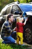 Middenleeftijdsvader met zijn de wasauto van de peuterzoon samen in openlucht Royalty-vrije Stock Foto