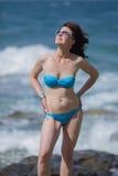 Middenleeftijdsvrouw in bikini het stellen met handen op heupen royalty-vrije stock afbeelding