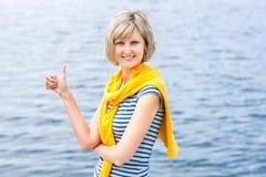 Middenleeftijdsvrouw die in openlucht duim omhoog gesturing Stock Afbeeldingen