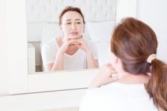 Middenleeftijdsvrouw die in spiegel op gezicht kijken Rimpels en het anti het verouderen concept van de huidzorg Selectieve nadru royalty-vrije stock afbeelding