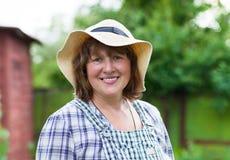 Middenleeftijdsvrouw in hoed het werken stock fotografie