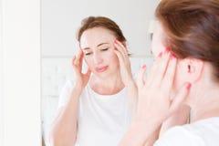 Middenleeftijdsvrouw met hoofdpijn in spiegel bij slaapkamer Selectief nadrukgezondheidszorg en overgangconcept De ruimte van het stock afbeelding