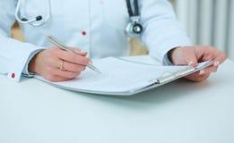 Middensectie van vrouwelijk artsenholding aanvraagformulier en het maken van nota's terwijl het raadplegen van patiënt Stock Foto's