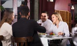 Middenstandmensen die van voedsel in koffie en het spreken genieten Stock Foto