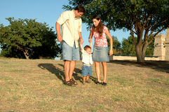 In the Middle. Happy american family, a diverse one, outside enjoying nature and spending time together. Family at the park. Little boy being picked up and swung royalty free stock photos