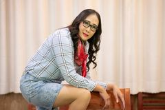 Middle adulthood long black hair Glasses woman wearing plaid shirt with cowboy bandana on Curtain background. Attractive cowgirl in checkered shirt with blank stock photo