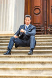 Middle Age American Businessman sitting on stairs outside vintag. Dressing in suit, necktie, a handsome, sexy, middle age businessman sitting on stairs in front Stock Photos
