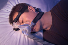 Middle age asian man with sleep apnea sleeping using CPAP machin. Middle age asian man with sleep apnea sleeping wering CPAP heargear connecting to air tube Royalty Free Stock Images