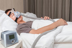 Middle age asian man sleeping in his bed wearing CPAP mask conne Stock Photography