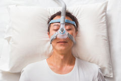 Middle age asian man sleeping in his bed wearing CPAP mask connecting to air hose, device for people with sleep apnea. Middle age asian man sleeping in his bed stock images