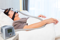 Middle age asian man sleeping wearing CPAP mask connecting to ai Royalty Free Stock Photo