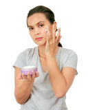 Middle Age Asian Woman apllies cream on her face. Royalty Free Stock Images