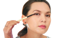 Middle age asian woman with make up brush. Royalty Free Stock Images