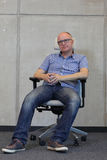 Middle age balding man with eyeglasses bad sitting position on chair in office. Front view Royalty Free Stock Photo