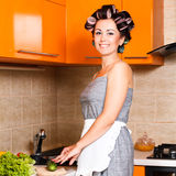 Middle-age beautiful woman in the kitchen with knife. Middle-age housewife in the kitchen cut vegetables Royalty Free Stock Images
