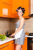 Middle-age beautiful woman in the kitchen with knife. Middle-age housewife in the kitchen cut vegetables Stock Photo