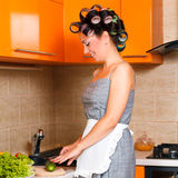 Middle-age beautiful woman in the kitchen with knife. Middle-age housewife in the kitchen cut vegetables Royalty Free Stock Photography