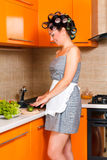 Middle-age beautiful woman in the kitchen with knife. Middle-age housewife in the kitchen cut vegetables Stock Image