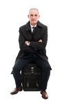 Middle age business man sitting on carry on luggage Stock Photos