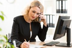 Middle-age business woman talking on the mobile phone in office. Portrait of smiling business woman. Royalty Free Stock Photo