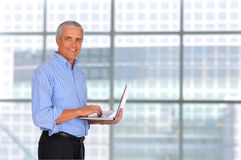 Middle Age Businessman Holding Laptop. Smiling Middle Aged Businessman holding laptop computer with in front of large window in modern office Royalty Free Stock Photos