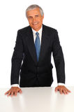 Middle Age Businessman leaning on desk Stock Image
