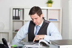Middle Age Businessman Seriously Reading a folder at the Table. Royalty Free Stock Images