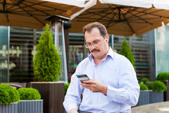 Middle age businessman using smartfone Stock Photos