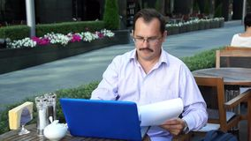 Middle age businessman works with docs stock footage