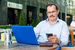 Middle age businessman works on laptop Stock Photos