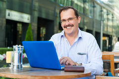Middle age businessman works on laptop Stock Images