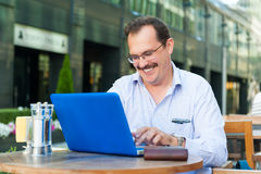 Middle age businessman works on laptop Royalty Free Stock Photo
