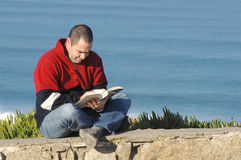 Middle age caucasion men reading a book. With the ocean for background Royalty Free Stock Images