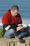 Middle age caucasion men reading a book. With the ocean for background Stock Images