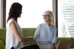 Middle age company executive manager shaking hands with young co. Blond attractive middle aged executive manager shaking hands greeting young specialist sitting royalty free stock photo
