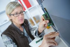 Middle age computer female technician working stock photo