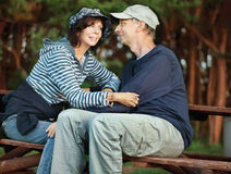 Middle-age couple sitting on a bench Stock Images
