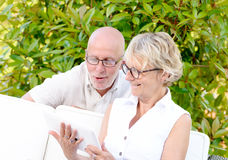 Middle age couple, smiling, using a tablet. In their garden stock photography